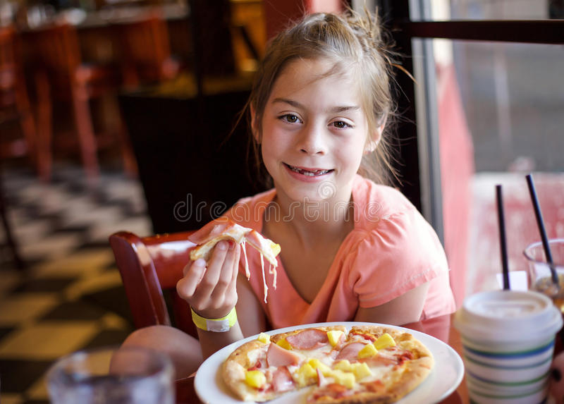 Cute little girl eating a piece of pizza in a restaurant stock photo