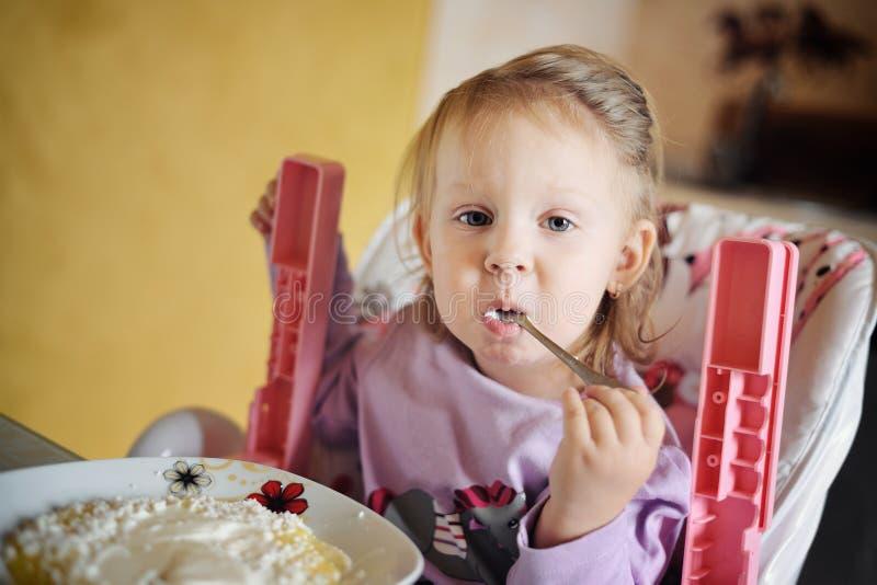Cute little girl eating porridge royalty free stock image