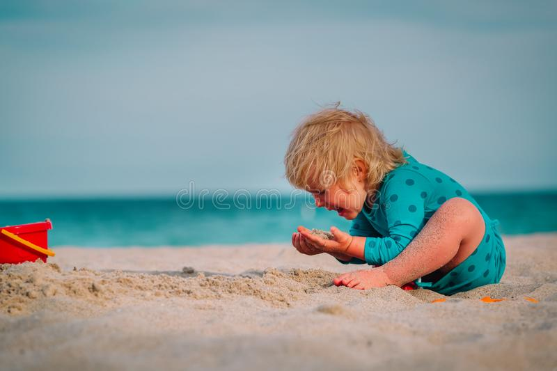 Cute little girl eating sand on beach royalty free stock photography