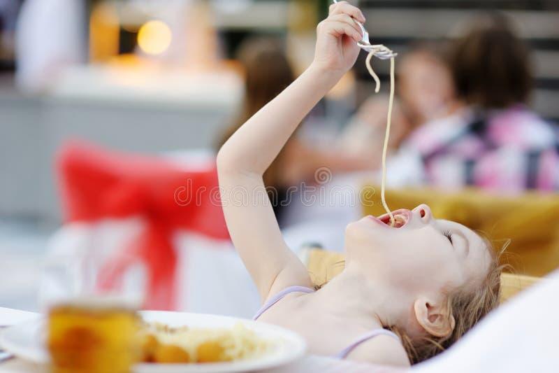 Cute little girl eating spaghetti royalty free stock photos