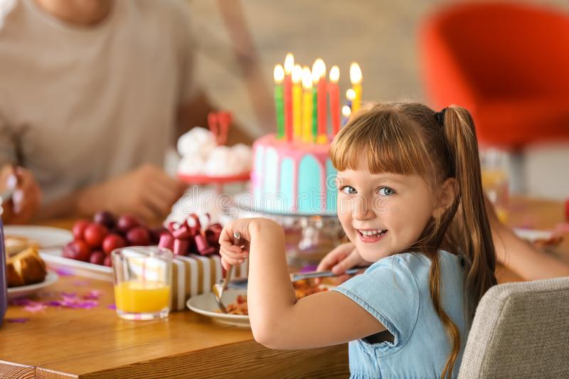 Cute little girl eating tasty pizza at birthday party stock photos