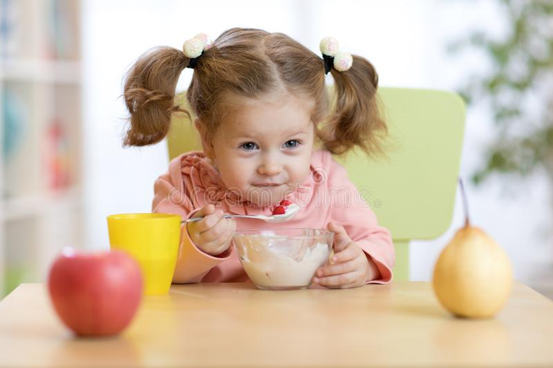 Cute little girl eating yogurt at home stock photos