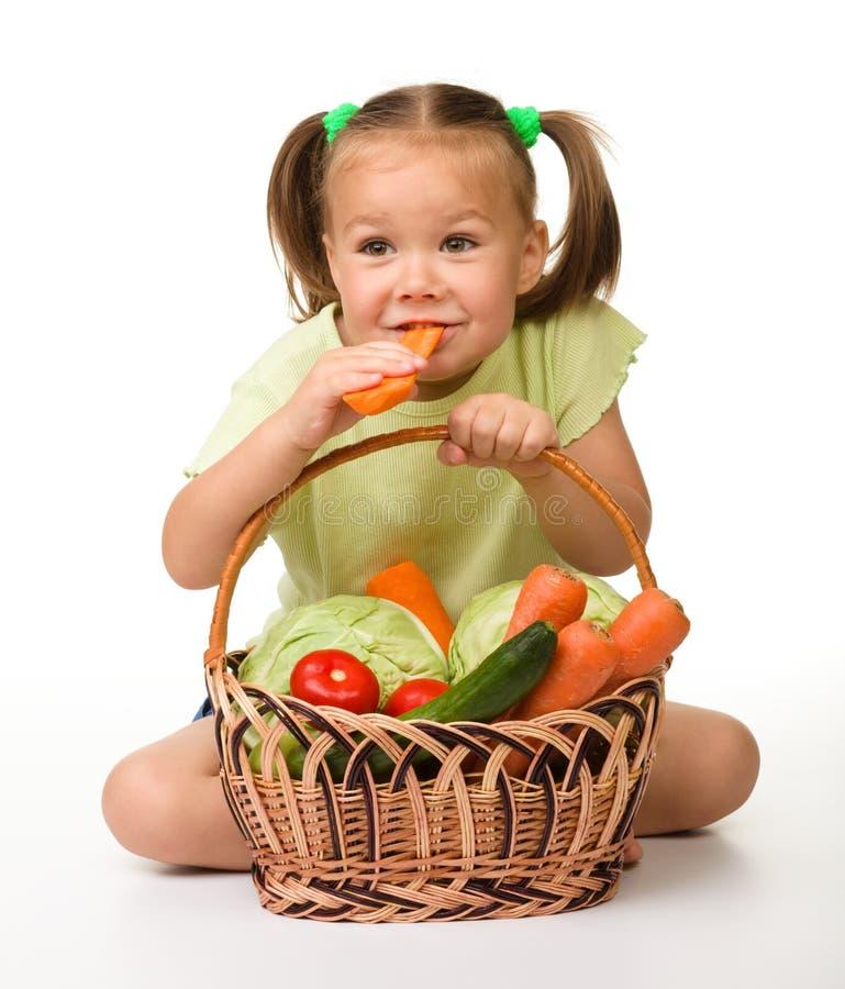 Cute little girl eats carrot stock images