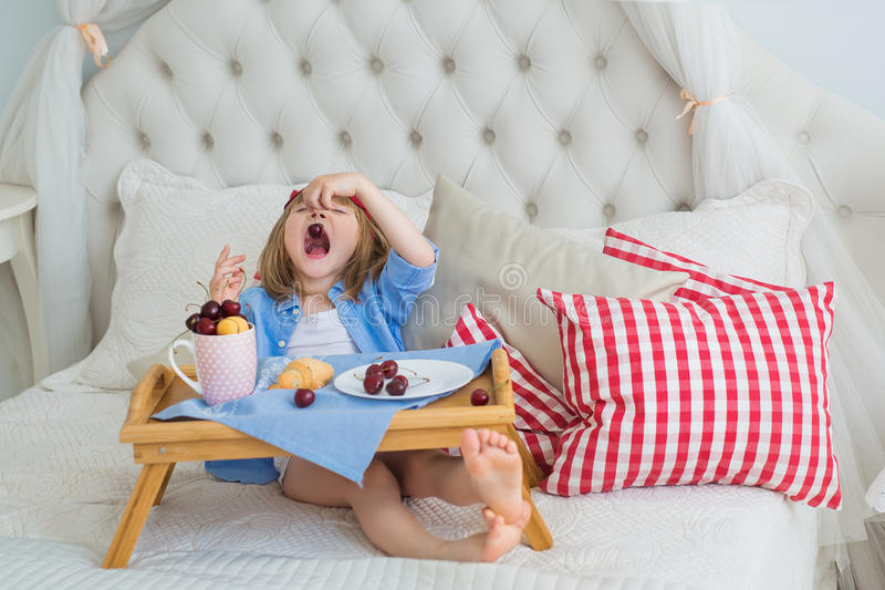 Cute little girl eats a cherry at breakfast on a bed stock image