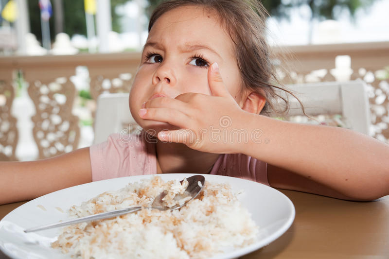 Cute little girl eats rice in a summer cafe royalty free stock photos
