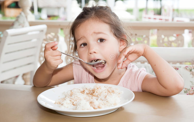 Cute little girl eats rice in a summer cafe stock images