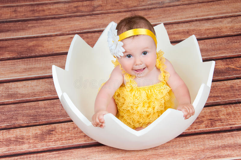 Cute little girl in the egg basket. View from above stock photos