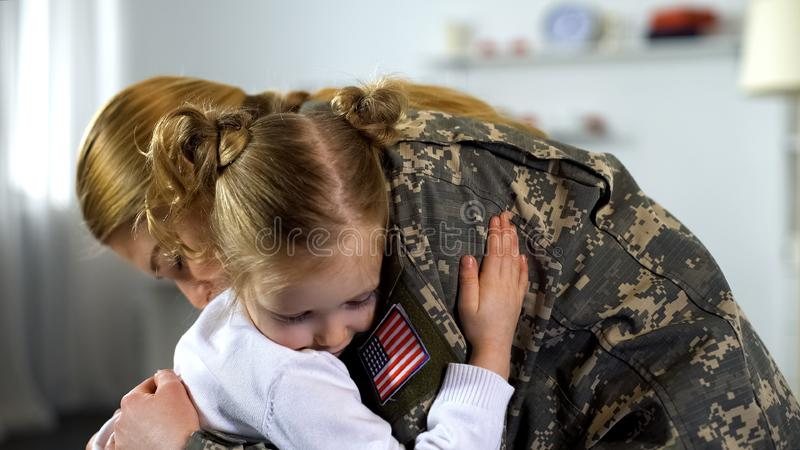 Cute little girl embracing soldier mother in uniform, armed forces duty parting royalty free stock image