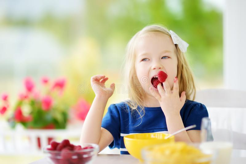Cute little girl enjoying her breakfast at home. Pretty child eating corn flakes and raspberries and drinking milk before school. Healthy nutrition for small royalty free stock photo