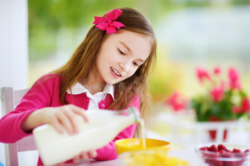 Cute little girl enjoying her breakfast at home. Pretty child eating corn flakes and raspberries and drinking milk before school. stock image
