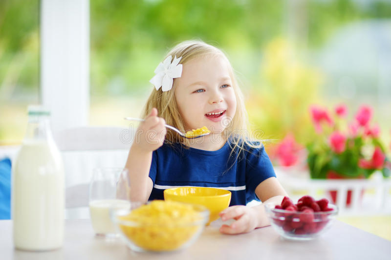 Download Cute Little Girl Enjoying Her Breakfast At Home. Pretty Child Eating Corn Flakes And Raspberries And Drinking Milk Before School. Stock Image - Image of bottle, grain: 90560479