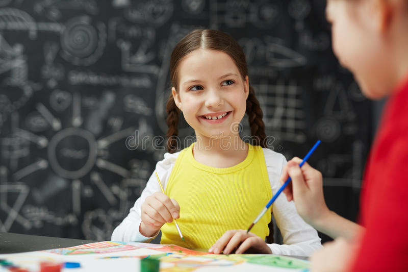 Cute Little Girl Enjoying Painting in Art Class. Portrait of cute smiling little girl painting pictures with friend during art lesson in school sitting against stock images
