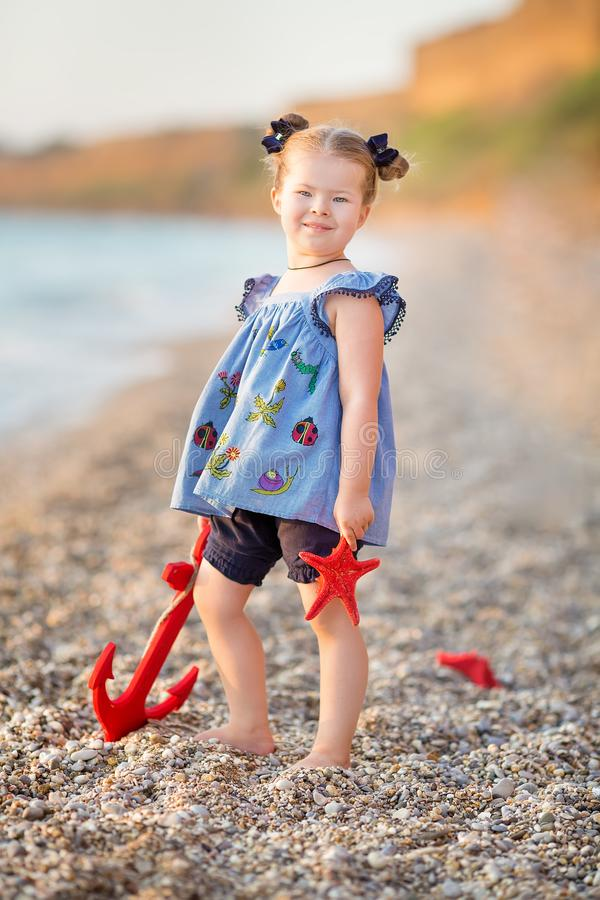 Cute little girl enjoying summer time on sea side beach happy playing with red star and tiny toy anchor on sand wearing nobby stock photography