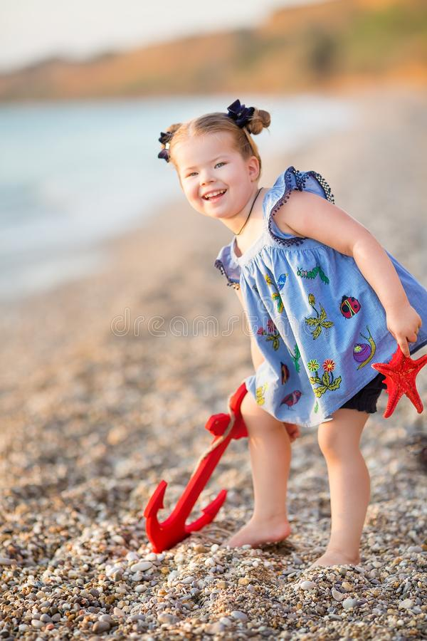 Cute little girl enjoying summer time on sea side beach happy playing with red star and tiny toy anchor on sand wearing nobby royalty free stock photo