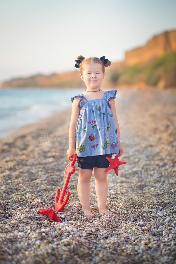 Cute little girl enjoying summer time on sea side beach happy playing with red star and tiny toy anchor on sand wearing nobby royalty free stock images