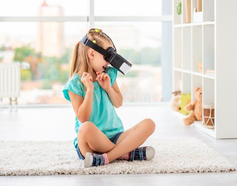 Girl enjoying virtual reality. Cute little girl enjoying virtual reality sitting home stock images