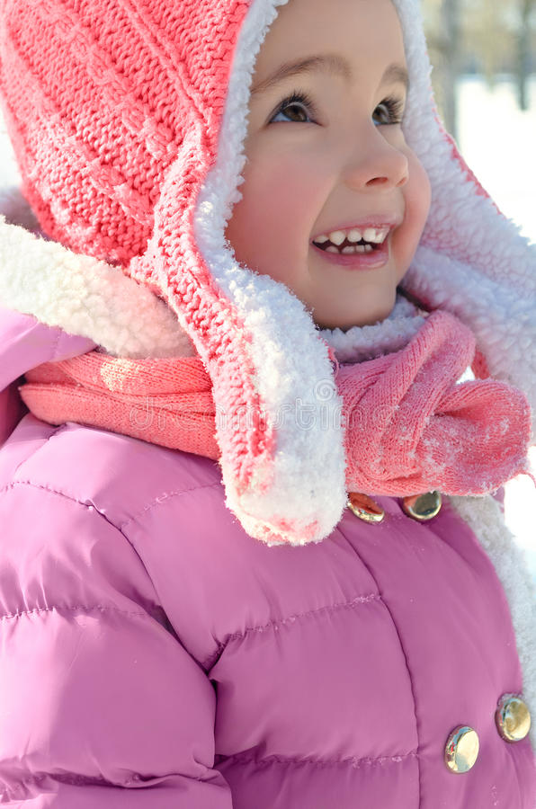 Cute little girl enjoying winter and snow dressed in warm bright stock image