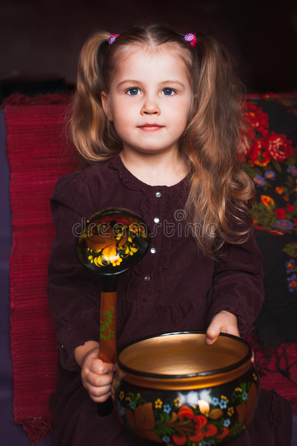 Cute little girl with ethnic dishes royalty free stock photography