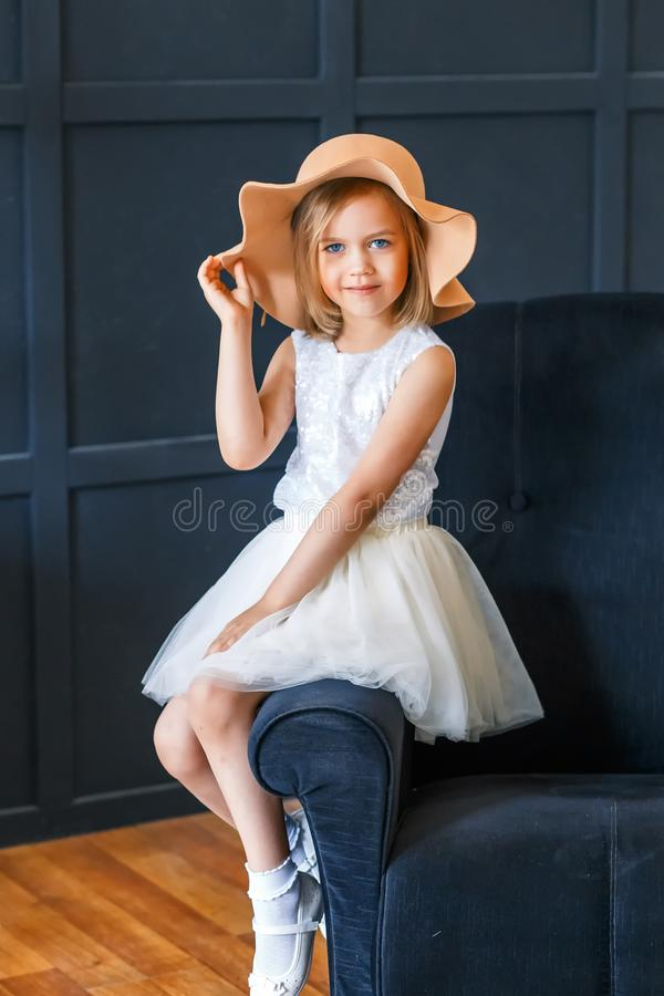 Cute little girl in fashionable hat with peonies in studio sitting on the armchair stock photo