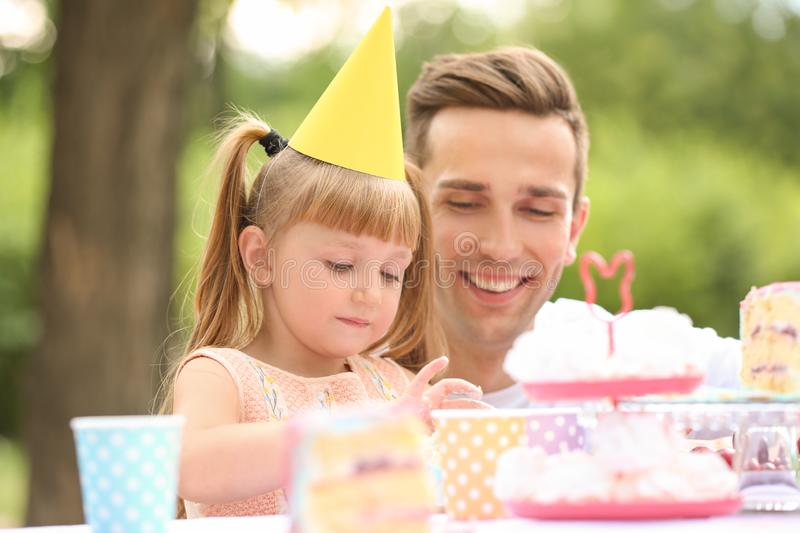 Cute little girl with father eating cake at birthday party outdoors royalty free stock photo