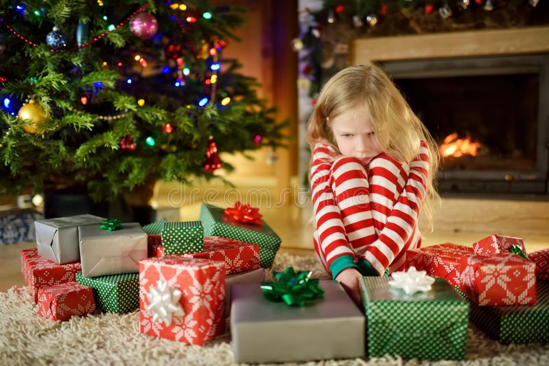 Cute little girl feeling unhappy with her Christmas gifts. Child sitting by a fireplace in a cozy dark living room on Xmas eve. Too many presents for Christmas stock photo