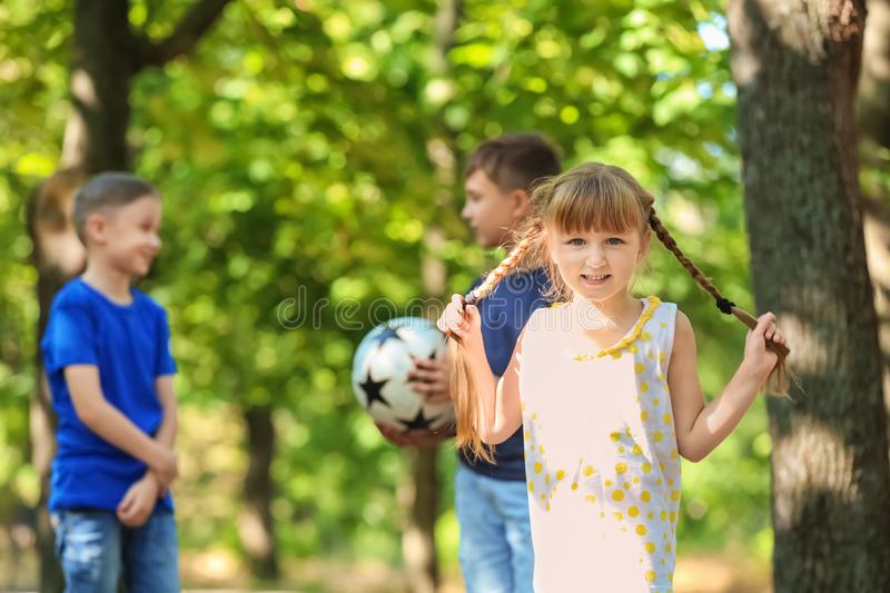 Cute little girl with friends in park stock image