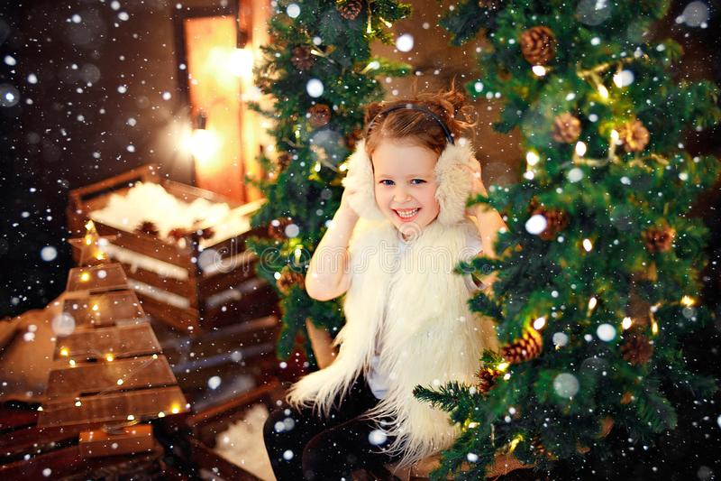 Cute little girl in fur earmuffs sitting near Christmas tree stock images