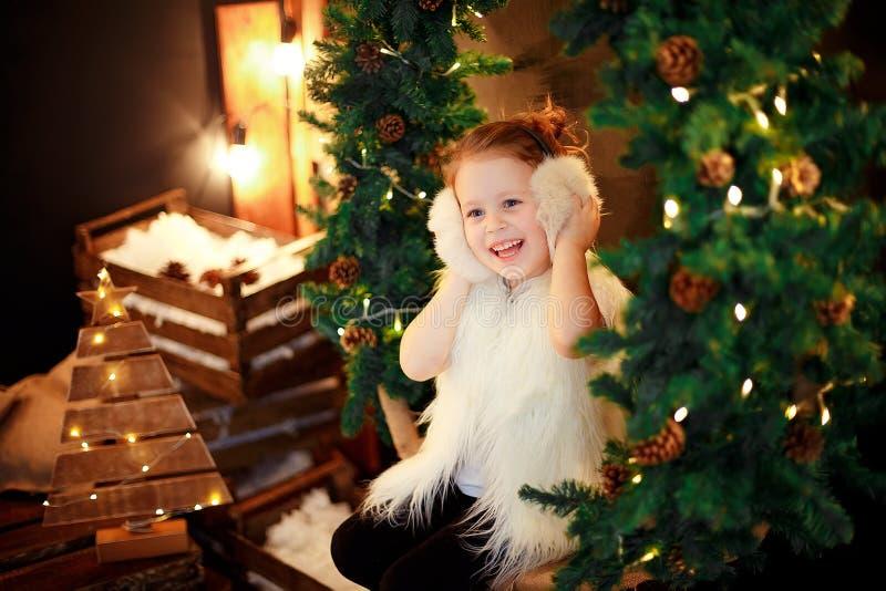 Cute little girl in fur earmuffs sitting near Christmas tree stock photos