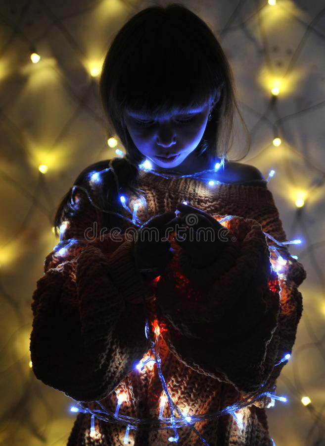 Cute little girl with a garland. Cute little girl with a lights of garland