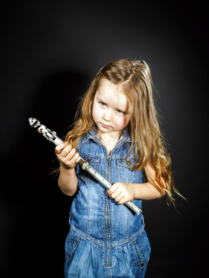 Cute little girl with gas spanner in her hands royalty free stock images