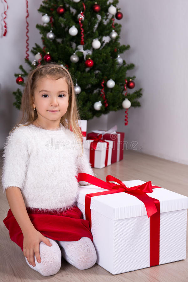 Cute little girl with gift box near Christmas tree at home stock image