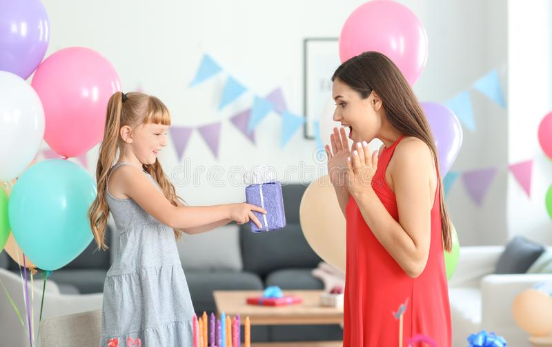 Cute little girl giving birthday present to her mother at home stock photography