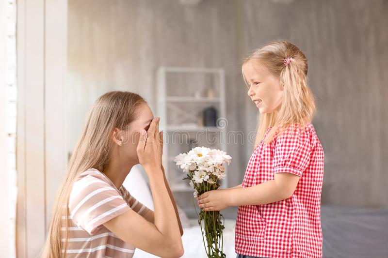 Cute little girl giving flowers to her mother at home royalty free stock photos