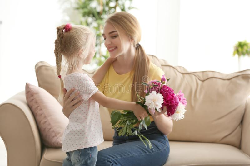 Cute little girl giving flowers to her mother at home stock photo