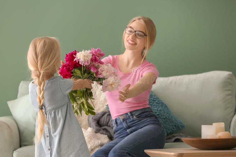 Cute little girl giving flowers to her mother at home royalty free stock photo