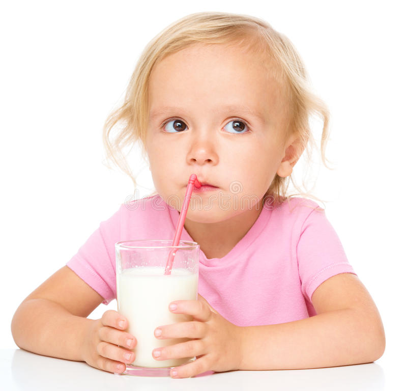 Cute little girl with a glass of milk. Cute little girl drinks milk using drinking straw, isolated over white royalty free stock images