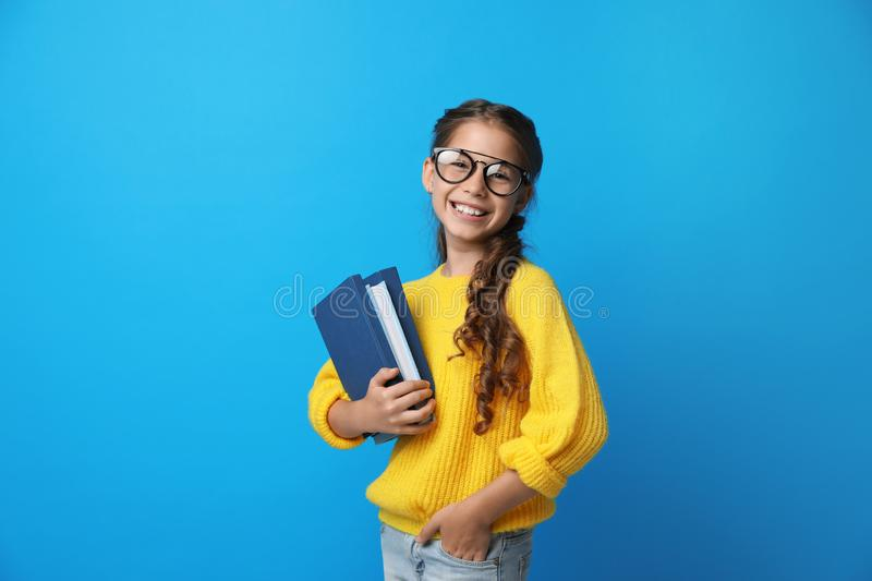 Cute little girl with glasses and books on blue background royalty free stock images