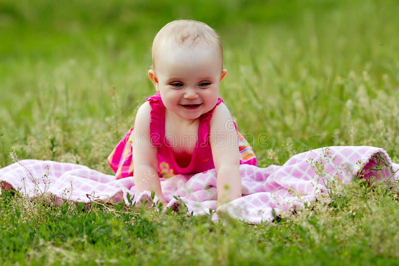 Cute little girl in the grass stock images