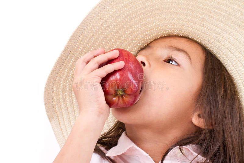 Cute little girl, hand holding, biting red apple royalty free stock image