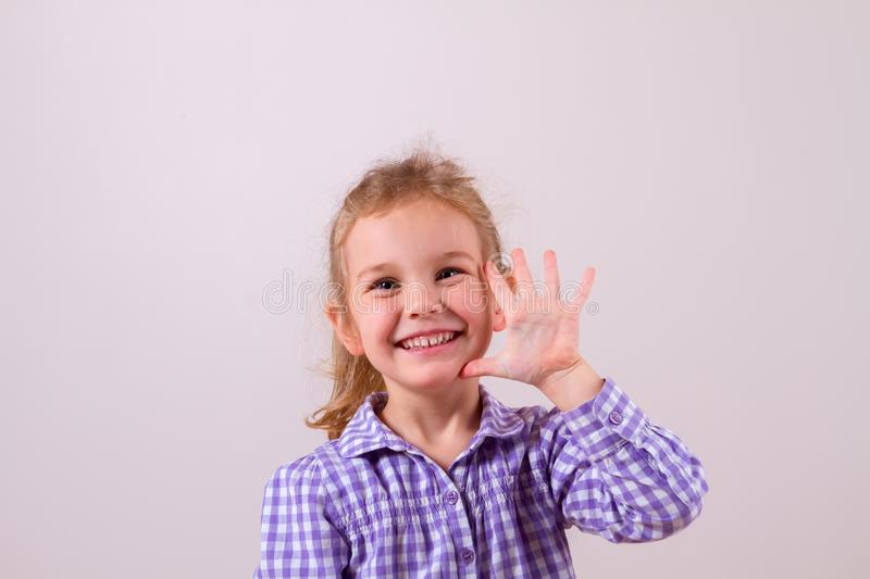 Cute little girl happily shows an open hand royalty free stock photos
