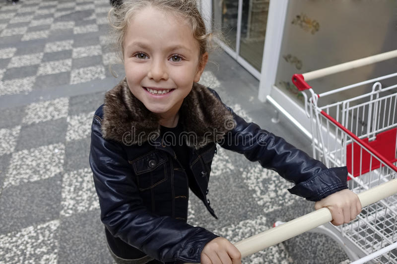 Cute little girl happy with shopping cart. royalty free stock photo