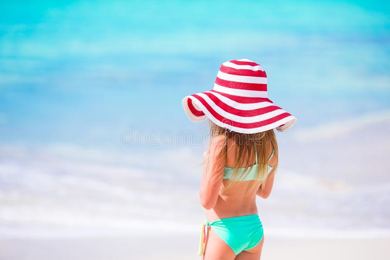 Adorable little girl in big red hat walking along white sand Caribbean beach. Cute little girl in hat at beach during caribbean vacation stock image