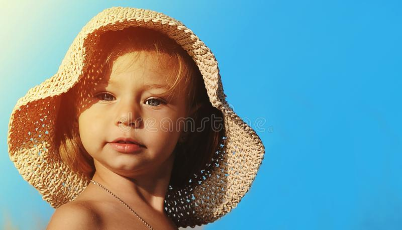 Cute little girl in hat on blue background. royalty free stock photography