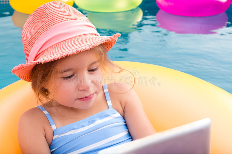 Cute little girl in hat using laptop while in pool royalty free stock images