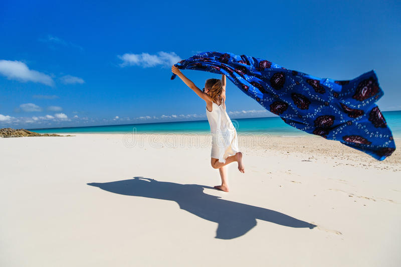 Cute little girl having fun on beach vacation. Cute little girl having fun running with sarong and enjoying vacation at tropical beach with white sand and stock image