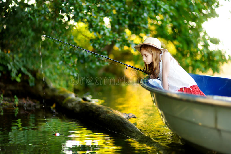 Cute little girl having fun in a boat by a river. At beautiful summer evening. Child fishing with a fishing rod on warm and sunny day stock photo
