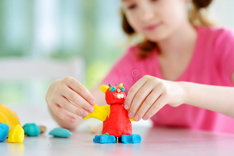 Cute little girl having fun with colorful modeling clay at a daycare royalty free stock image