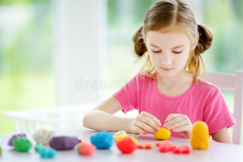 Cute little girl having fun with colorful modeling clay at a daycare. Creative kid molding at home. Child play with plasticine or dough royalty free stock photography