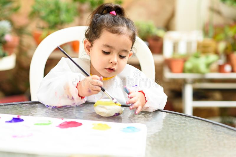 Cute little girl having fun, coloring with brush, playing and painting. Preschooler with paint at garden. royalty free stock image