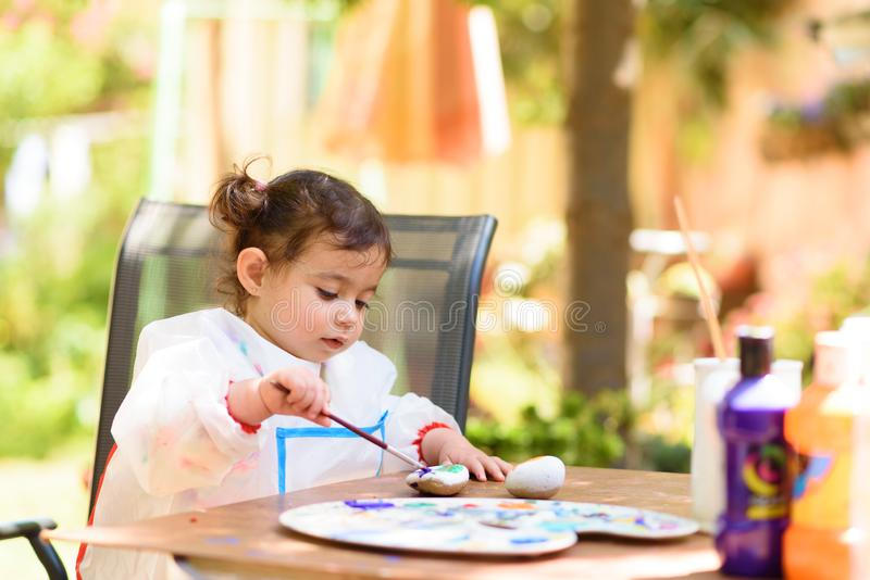 Cute little girl having fun, coloring with brush, writing and painting at summer or autumn garden. stock photo
